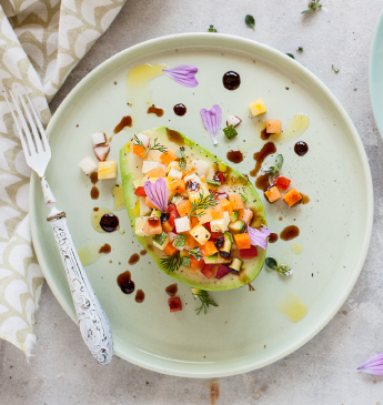 Avocado filled with fruit and vegetables topped with drops of Balsamic Vinegar of Modena PGI