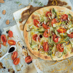 Pizza with tomato confit, puntarelle, almonds and orange