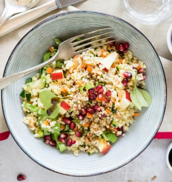 Cous cous salad with raw vegetables, pomegranate and walnuts