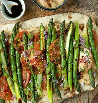 Schiacciata croccante con asparagi, pomodori e hummus di arachidi